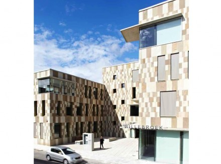 Janelas marcantes na fachada tornam o prédio óticamente mais aberto. Quebra-sóis em forma de sacadas tornam a atmosfera convidativa.