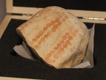 Fundstück aus dem Hohlen Fels bei Schelklingen, bemalt mit dunkelroten Punkten in zwei Doppelreihen.