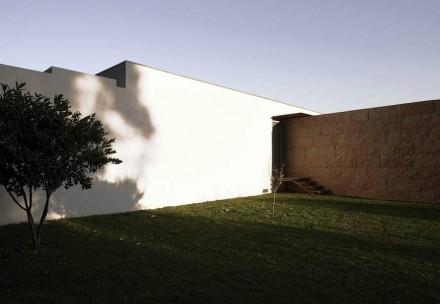 Dietro alla casa si trova la parte della piscina, davanti l'accesso con garage, giardino e ufficio.