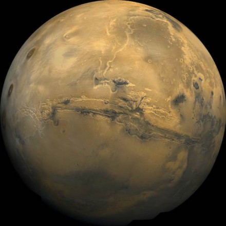Global mosaic of 102 Viking 1 Orbiter images of Mars taken on orbit 1,334, 22 February 1980. The images are projected into point perspective, representing what a viewer would see from a spacecraft at an altitude of 2,500 km. At center is Valles Marineris, over 3000 km long and up to 8 km deep. Note the channels running up (north) from the central and eastern portions of Valles Marineris to the area at upper right, Chryse Planitia. At left are the three Tharsis Montes and to the south is ancient, heavily impacted terrain. Photo: NASA / USGS / Wikimedia Commons