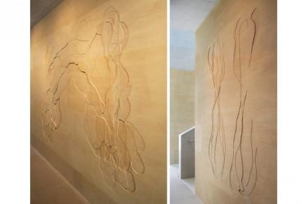 Die Wand befindet sich an einem Gang entlang der Rückseite des Hörsaals. 104 Platten aus dem französischen Kalkstein Pierre de Jaumont in verschiedenen Größen wurden verwendet.