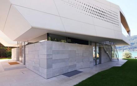 La pared de la casa llega a ras de suelo recubierta con placas de diverso tamaño de piedra caliza Gala de los montes Jura.