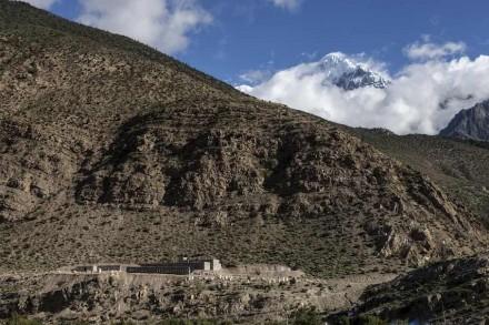 La nostra foto mostra il Nilgiri-Nord nell' Himalaya, alto 7061 m e situato nel massiccio di Annapurna. Ciò nonostante qui non si tratta di questa montagna, ma dell' edificio basso sulla foto in basso a sinistra che si distingue quasi per niente dal deserto di rocce circostante.