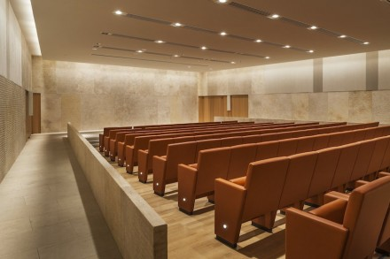 The Auditorium with seating for 150 persons is also adorned with the golden limestone variant. For aesthetical and acoustical reasons, textile and wood surfaces were introduced between the stone slabs.