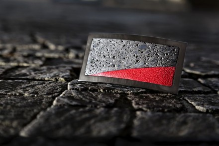"""... """"Lava"""" combines dark volcanic material and bright red leather, framed in Ruthenium."""