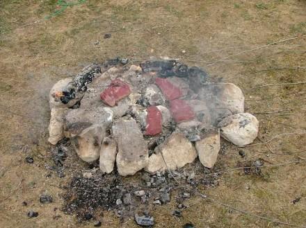 Grillen wie die Eiszeitmenschen: Experimentelle Feuerstelle zur Nahrungszubereitung auf heißen Steinen. Die Messdrähte rechts führen zu einem Computer, der die Brenntemperatur aufzeichnet Foto: RGZM-Monrepos/Frank Moseler