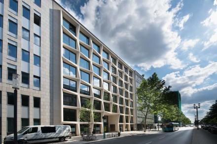 En primer lugar, la fachada está rodeada de una especie marco exterior, que produce un efecto distanciador frente a los edificios de alrededor.