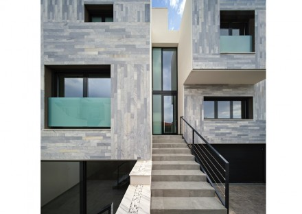 The motion is unobtrusive because the façade is recessed in the middle section of the house which is made of glass exclusively, allowing light to flow freely into the house but keeping the heat out.