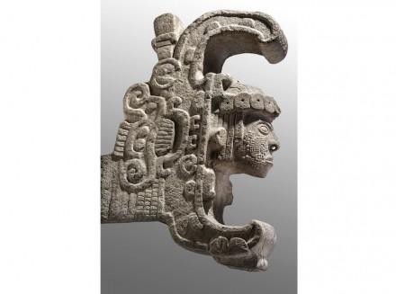 Die Königin von Uxmal. Kalkstein, 600-900 n. Chr, INAH, Mexiko-Stadt. Die Skulptur stammt von der Hauptfassade der Zauberer-Pyramide: Aus einem stilisierten, aufgerissenen Schlangenmaul kommt ein menschlicher Kopf hervor mit Ohrschmuck, einer durchstochenen Nase und einer Kopfbedeckung aus Jadescheiben. Dargestellt ist vielleicht ein Ritual, bei dem der Herrscher symbolisch von einer Boa verschlungen worden war, um mit den Kräften eines Schamanen wiederzukehren.