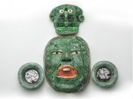 Begräbnismaske mit Ohrsteckern und Kopfschmuck. Jade, Obsidian und Muschel, 600–900 n. Chr., INAH, Campeche. Auf dieser Maske sind die drei Ebenen des Kosmos dargestellt: durch den Urzeitvogel auf der Kopfbedeckung, durch das Gesicht des begrabenen Würdenträgers und durch den Jaguargott der Unterwelt. Die Linie aus Spondylus calcifer, einer purpurfarbenen Muschel, umrahmt das Gesicht und verweist auf die unterirdische Wasserwelt.