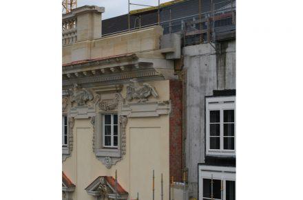 Von der Humboldt-Box aus kann man noch sehen, wie die Fassade aufgebaut ist: vor der Betonwand des Gebäudes befindet sich eine Klinkermauer, in die die Sandsteinelemente eingemauert sind. Das Gesims ist auf diese Mauer aufgesetzt.