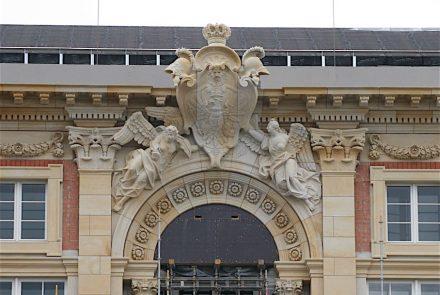 Das Portal V (links neben dem farbigen Fassadenteil) zeigt die reiche Natursteinzier über den Zugängen. In der Schlossbauhütte stellten Steinbildhauer die besonderen Elemente wieder her.