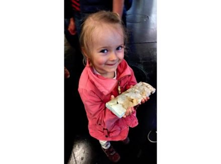 A little girl holding a piece of Desert Grey. Photo taken at the Stone+tec fair in Nuremberg, 2015.
