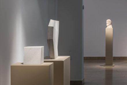 Blick in die Ausstellung. Im Hintergrund die älteste Arbeit, ein Kopf aus Kalkstein aus dem Jahr 1972, im Vordergrund die jüngste Arbeit, ein Marmorwürfel aus dem Jahr 2017.