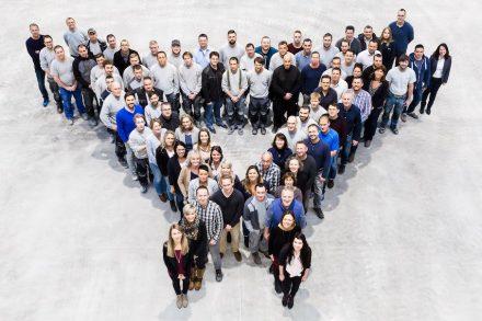 Mitarbeiter von KMD stellen das Logo des Unternehmens nach. Foto: KMD