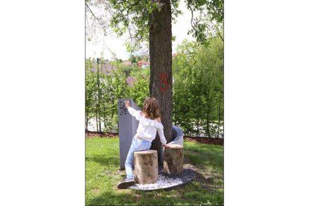 """Bei der mit dem 1. Preis der Kategorie A ausgezeichneten """"Baumbestattung"""" windet sich das Grabdenkmal aus Schremser Granit um einen Baum; in die Stirnseite ist ein Mühlespiel mit grauen und weißen Kieselsteinen eingearbeitet."""