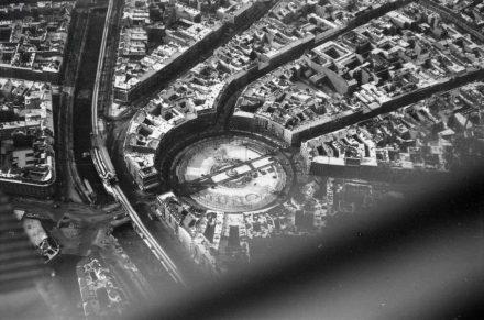 """Luftaufnahme aus dem Jahr 1933: links die U-Bahn, daran anschließend das Rondell des Mehringplatzes und aus ihm hervorgehend die Friedrichstraße. Foto: Walter Mittelholzer / <a href=""""https://commons.wikimedia.org/""""target=""""_blank"""">Wikimedia Commons</a>"""