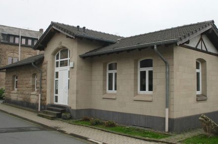 """Ehemaliges Bahnhofsgebäude der Brohltalbahn in Weibern, um 1900, aus Weiberner Tuffstein über Basaltlavasockel, heute """"Steinmetzbahnhof""""."""