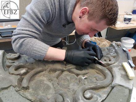 Ein Kursteilnehmer bei der Rissinjektion an einem Spitzbogentympanon aus Molasse Sandstein.