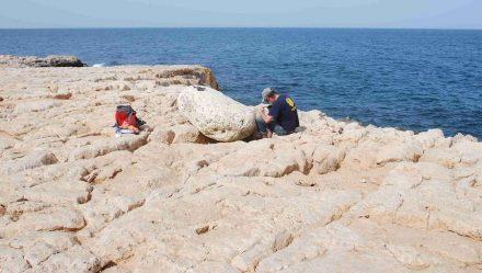Einer der Wissenschaftler untersucht einen Findling, der vom Tsunami auf die Klippen geschleudert worden war. Foto: Gösta Hoffmann/Uni Bonn