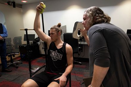 Wyatt Walker, former North Carolina State University basketball player, models with a bunch of grapes at the team's practice facility in Raleigh while Heather Pendrak of Pendragon 3D scans his arm.