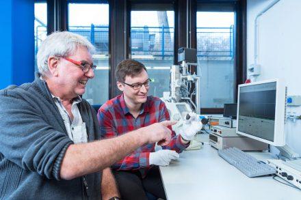 """Die Planetologen Prof. Dr. Addi Bischoff (li.) und Markus Patzek mit dem Meteoriten """"Flensburg"""" vor dem Rasterelektronenmikroskop. Foto: Universität Münster / Michael C. Möller"""