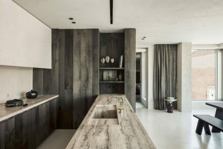 This elegant kitchen designed by Arjaan De Feyter, based in Wijnegem, Belgium, is marked by an interesting contrast between slabs of grey travertine, concrete and stained ash wood.