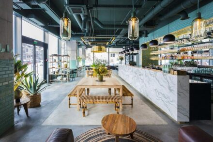 The Kane World Food Studio restaurant, designed by Bogdan Ciocodeica in Bucharest as an urban tropical oasis, presents a unique combination of materials: the large marble counter, concrete floor and pillars, wooden furniture, with brass mirrors and finishes.
