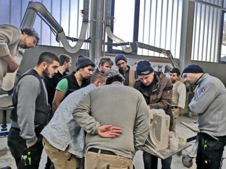 Die Kursteilnehmer verfolgen eine praktische Demonstration in der Werkstatt.