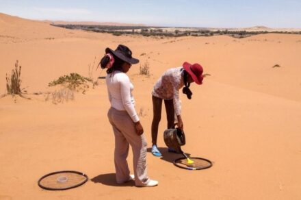 Students Rosalia Tshikesho (L) and Etuna Iyambo (R) simulate a rain shower prior to making measurements of soil carbon dioxide release in the Namib Desert. Credit: Throop/ASU