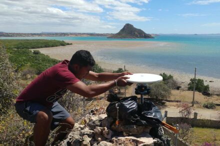 Geosciences doctoral student Tahiry Rajaonarison from the team of scientists sets up a GPS instrument in northern Madagascar in this 2016 photograph. Behind Tahir is the Indian Ocean and a rock island. Photo: Rina Andrianasolo