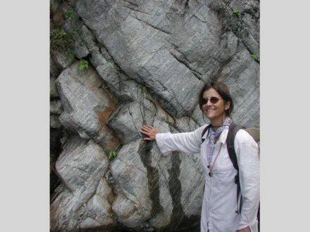 Suzanne Baldwin, Thonis Family Professor, examining a gneiss, a type of metamorphic rock on a field expedition to Goodenough Island, Milne Bay Province, Papua New Guinea.