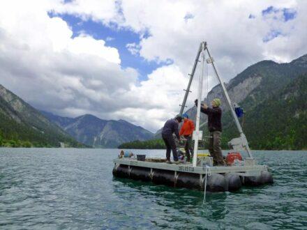 Das Team vom Institut für Geologie entnimmt von einer schwimmenden Bohrplattform bis zu 8 Meter lange Bohrkerne aus dem Plansee im Tiroler Bezirk Reutte. Foto: Jasper Moernaut