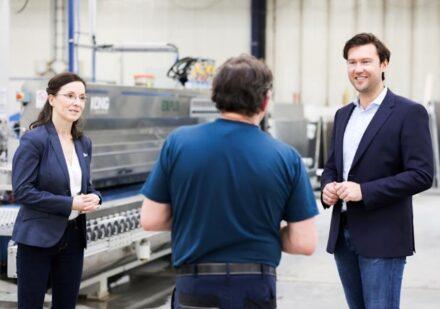 Das neue Vorstandsteam (links: Christin Bergmann, rechts: Oliver Schleich) im Gespräch mit einem Produktionsmitarbeiter.