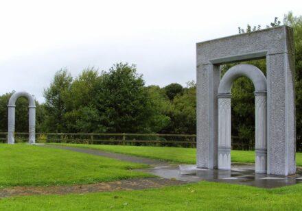 """Martha Quinn: """"Newgate, Rivergate"""". Zwei Kalksteinbögen auf einem kleinen Platz."""