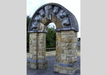 """Seamus Dunbar und Niall Walsh: """"Roscrea Arch"""". Bogen aus Sand- und Kalkstein mit Tier- und Menschenköpfen."""