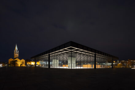 Die Neue Nationalgalerie bei Nacht mit dem Turm von Sankt Matthäus im Hintergrund. Foto: Thomas Bruns / BBR